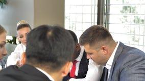 Multiraciaal commercieel team die samen businessplannen in langzame motie bespreken stock footage