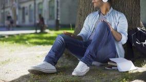Multiraciaal mannetje die in hoofdtelefoons onder boom zitten, die aan favoriete muziek luisteren stock videobeelden