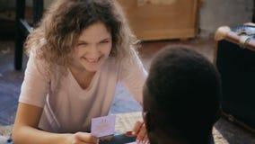 Multiraciaal paar die het raadsspel samen spelen De man en de vrouw maken samen de taak op kaart en lach stock footage