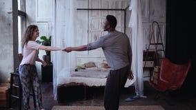 Multiraciaal paar in pyjama's die, hebbend pret samen in ochtend dansen Vrouwensprongen op man handen, kussen Langzame Motie stock footage
