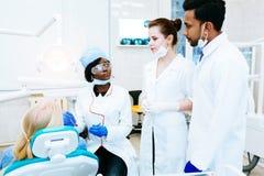 Multiraciaal tandteam met patiënt in tandkliniek Stilleven van groene appel, verse munt en de lichte kaars van T tegen een witte  Royalty-vrije Stock Afbeelding