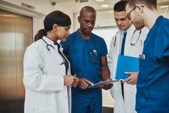 Multiraciaal team van artsen die een patiënt bespreken stock foto's