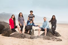 Multiracial экстренныйому выпуску нужна семья сидя на больших утесах вдоль пляжа стоковое фото rf