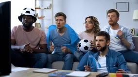 Multiracial аргентинские друзья наблюдая футбольный матч дома, единение стоковое изображение rf