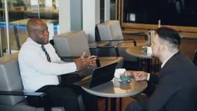 2 multiracial бизнесмена в официально одеждах усмехаясь, показывать и обсуждая их запуск в просторном кафе во время видеоматериал