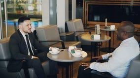 2 multiracial бизнесмена сидя, усмехаясь и обсуждая их запуск в воздушном кафе во время времени обеда afoul сток-видео