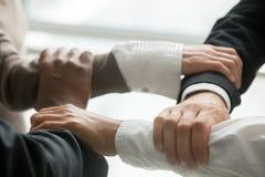 4 multiracial бизнесмены держа каждые другие запястья руки, clo Стоковые Фотографии RF