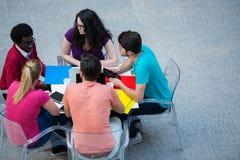 Multiracial группа в составе молодые студенты изучая совместно Высокая угловая съемка молодые люди сидя на таблице Стоковые Фотографии RF