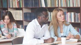 Multiracial группа в составе студенты университета посещая библиотеку на периоде встречи видеоматериал