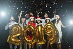 Multiracial друзья держа золотой номер раздувают на партии стоковые изображения rf