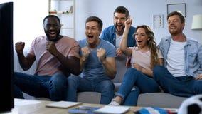 Multiracial друзья празднуя цель, наблюдая футбол дома, единение стоковые фотографии rf