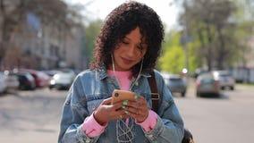 Multiracial женщина слушая музыку в городе на весеннем времени видеоматериал