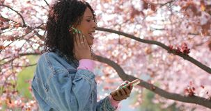 Multiracial женщина слушая музыку в парке на весеннем времени акции видеоматериалы