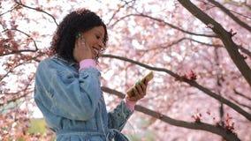 Multiracial женщина слушая музыку в парке на весеннем времени сток-видео