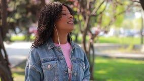 Multiracial женщина слушая музыку в парке на весеннем времени видеоматериал