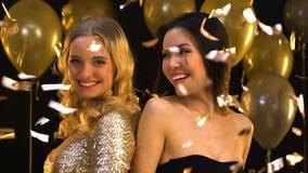 Multiracial женщины усмехаясь и имея потеху на партии под падая confetti, выпускном вечере сток-видео