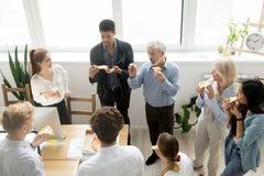 Multiracial коллеги есть пиццу и говоря на корпоративном  Стоковые Изображения