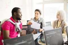 Multiracial коллеги обсуждая в офисе Стоковое Изображение