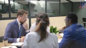 Multiracial команда коллективно обсуждать проект в конференц-зале офиса сток-видео