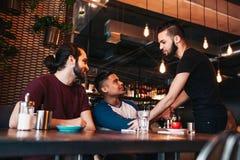 Multiracial люди встречая их друга в Лаунж-баре Реальные эмоции лучших другов счастливых для того чтобы увидеть один другого прия стоковое фото rf
