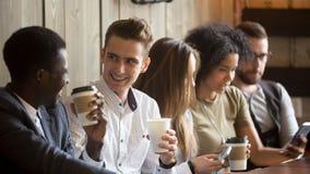 Multiracial люди говоря выпивая смертную казнь через повешение кофе с usi друзей Стоковые Изображения