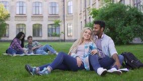 Multiracial пары ослабляя на траве, говоря и усмехаясь, первая влюбленность, студенты видеоматериал