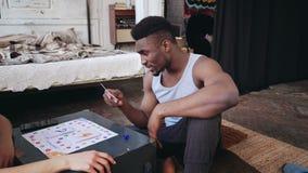 Multiracial пары сидя на поле в пижамах и играя настольную игру совместно Ход человека кость и взятие чешет Стоковые Фотографии RF
