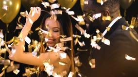 Multiracial пары flirting и танцуя под падая confetti, местом для одноразового выступления видеоматериал