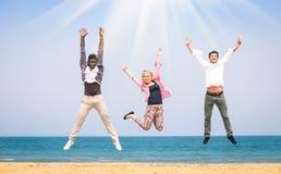 Multiracial друзья скача на пляж Стоковое Изображение RF