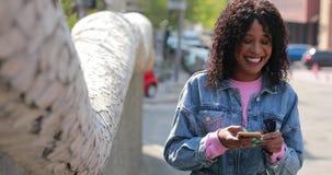 Multiracial сообщение чтения женщины в телефоне со смехом в городе видеоматериал
