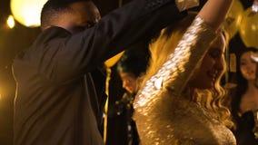 Multiracial танцы человека и женщины на партии под падая confetti, торжестве акции видеоматериалы