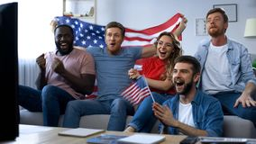 Multiracial American fans watching match on TV at home, celebrating team goal stock images