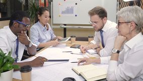 Multiracial architect colleagues brainstorming building blueprints in office. stock footage