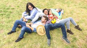 Multiracial best friends having fun at meadow picnic - Happy friendship fun concept with young people millenials sharing time. Together with mobile phone royalty free stock photography