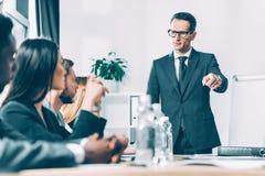multiracial biznesmeni słucha lider zespołu w sali konferencyjnej podczas gdy on wskazuje obraz stock