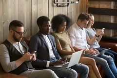 Multiracial black and white people sitting on couch using device. Multiracial black and white people sitting on couch ignoring each other immersed in phones and Stock Photo