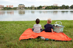 Multiracial boys have picnic. By a lake Stock Image