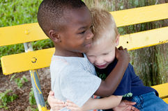Multiracial boys hug each other. On a yellow park bench Stock Photography