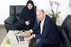 Multiracial Business meeting between a Senior Businessman & a woman wearing Hijab. Multiracial Business meeting between a Senior Businessman & a women Stock Photography