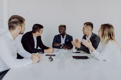 Multiracial business people applauding sitting at conference table, diverse team clapping hands after group meeting. multinational royalty free stock photos