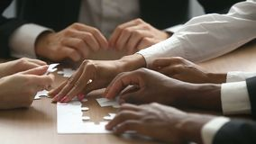 Business people trying to connect jigsaw puzzle, bad teamwork concept. Multiracial business people hands unsuccessfully trying to assemble jigsaw puzzle at stock video