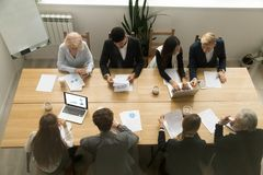 Multiracial business people working together at conference table. Multiracial young and old business people sitting at conference table meeting in office royalty free stock photos