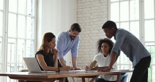 Multiracial business team brainstorm on paperwork at office meeting table