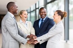 Multiracial business team together. Cheerful multiracial business team putting their hands together royalty free stock images
