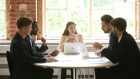 Multiracial businessmen listening to female company boss talking holding meeting. Multiracial businessmen listening agreeing with businesswoman speaking about stock footage