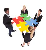 Multiracial businesspeople holding jigsaw puzzle Stock Image
