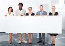 Multiracial businesspeople holding placard Stock Image