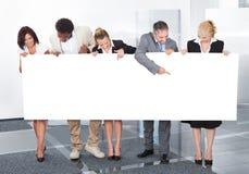 Multiracial businesspeople holding placard Stock Photos