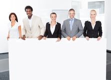 Multiracial businesspeople holding placard Royalty Free Stock Photography
