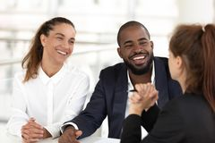 Friendly human resources managers interviewing vacancy candidature. Multiracial businesspeople sitting at desk in modern office room, smiling diverse teammates royalty free stock photo